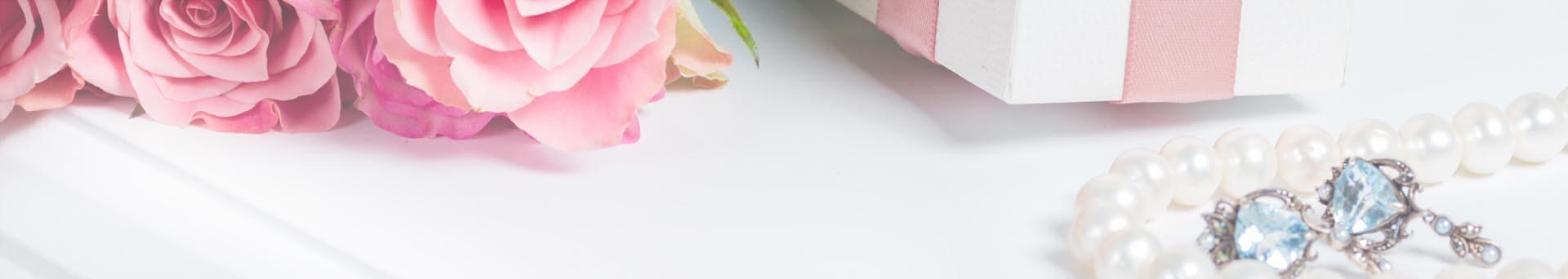 prezent z różową wstążką, biżuteria i róże