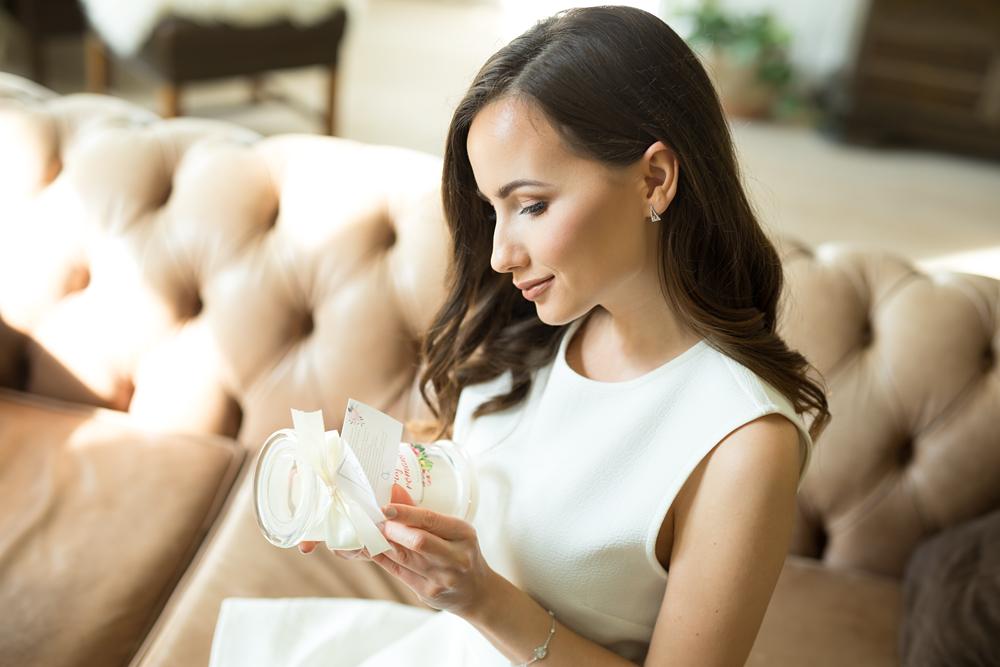 uśmiechnięta kobieta ze świecą zapachową