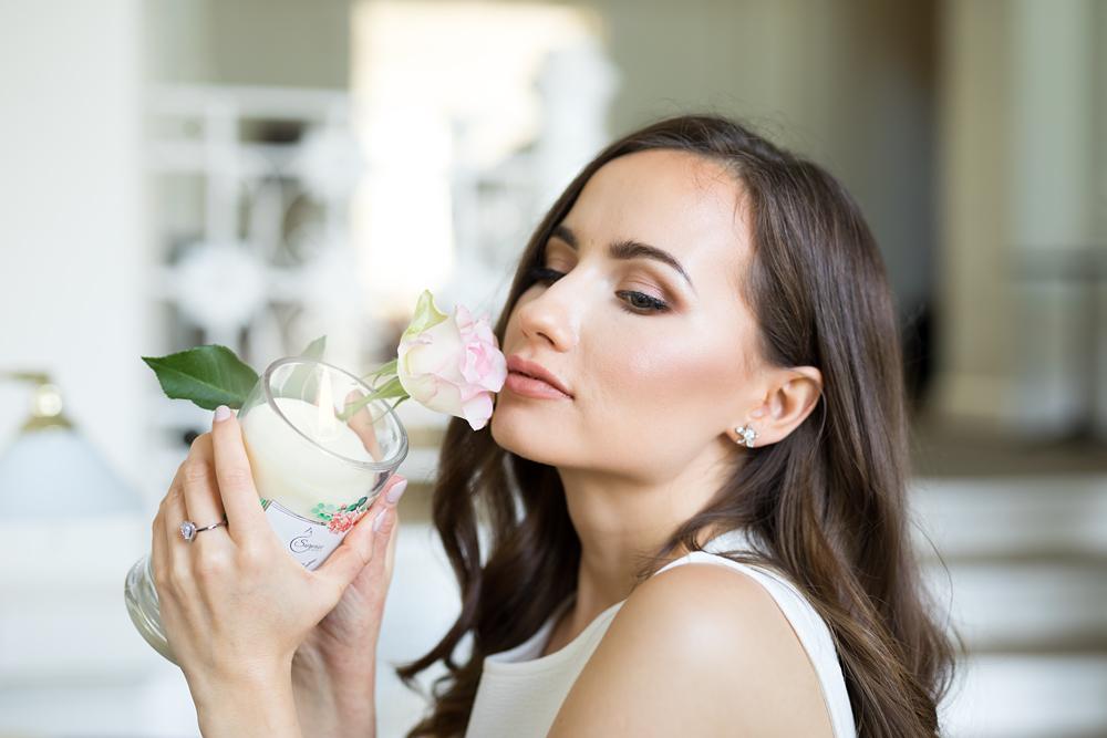 kobieta ze świecą zapachową i różą