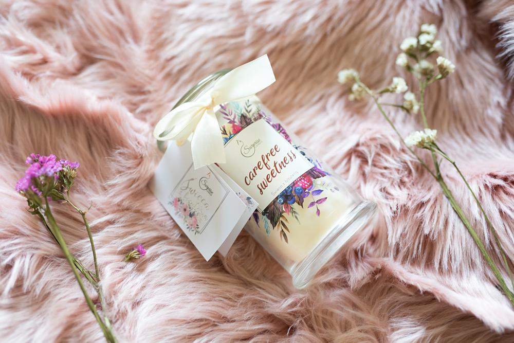 świeca zapachowa z kwiatami na różowym tle