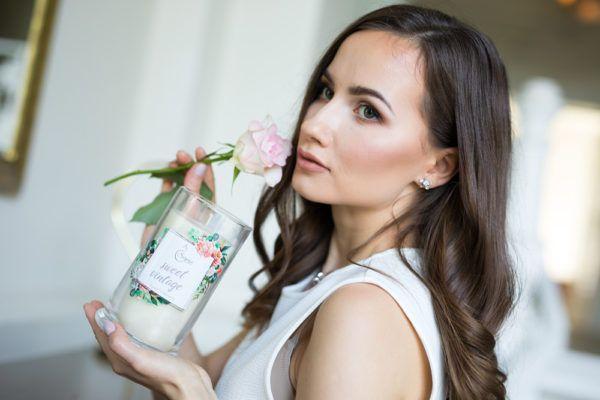 kobieta trzymająca świecę zapachową i różę