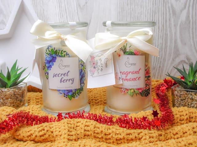dwie świece zapachowe surprise candle związane wstążkami